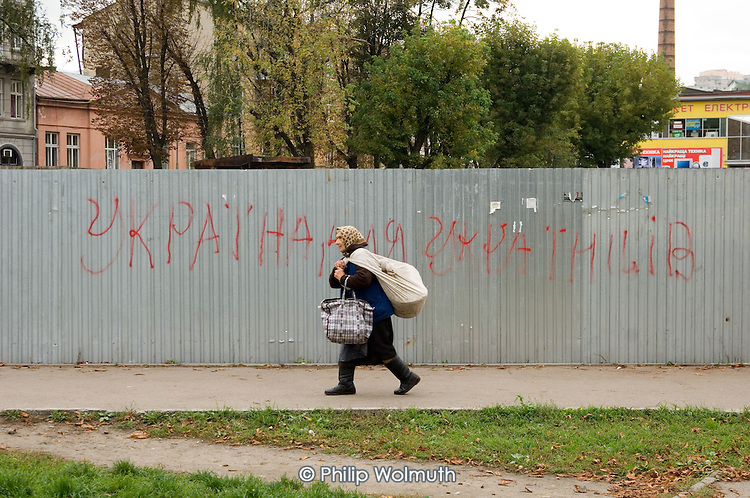 "An elderly peasant woman in Lviv walks past nationalist graffiti which reads ""Ukraine for the Ukrainians""."