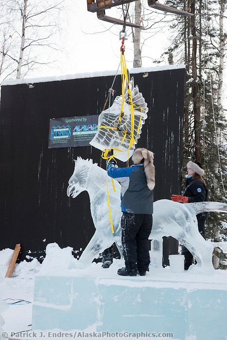 """Jeff Stahl and Heather Brice, USA, get assistance from a crane to hoist the wings on the multi block sculpture titled """"Guardian Angel of Mischief"""" for the 2009 World Ice Art Championships in Fairbanks, Alaska. Team members: Heather Brice, Kevin Gregory, Jeff Stahl, Steve Cox"""