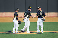 (L-R) Wake Forest Demon Deacons outfielders Joey Rodriguez (8), Jonathan Pryor (11), and Stuart Fairchild (4) shake hands after their win over the Miami Hurricanes at Wake Forest Baseball Park on March 22, 2015 in Winston-Salem, North Carolina.  The Demon Deacons defeated the Hurricanes 10-4.  (Brian Westerholt/Four Seam Images)