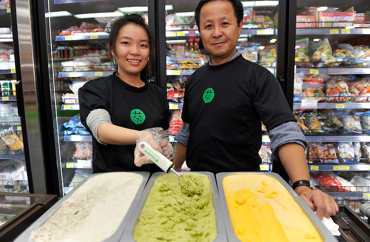 Shop assistant Irene (L) and Maeda-en CEO and CQO Taku H. Maeda pose with tubs of green tea (centre) and black sesame (L) ice cream and mango sorbet (R) during the launch of Maeda-en's range of green tea and black sesame ice cream and mango sorbet at Formosa Asian Market, Sunnybank, , Brisbane, Queensland, Saturday, October 01, 2011. (Photo by John Pryke/JKDImagery)