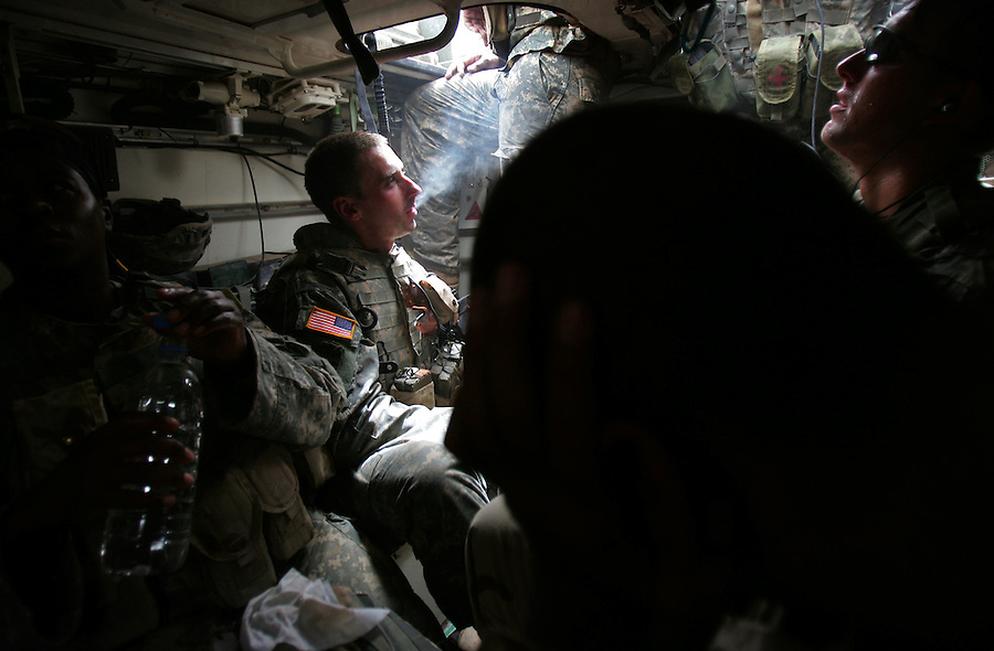 US soldier feeling the effects of 120 degree temperatures and body armor sit wearily in the troop compartment of a Stryker armored vehicle at the end of a long sweltering day's work  in Ahdamiyah - a largely Sunni district in central Baghdad - on the first day of a large-scale security sweep by US and Iraqi soldiers and police on Sunday August 27, 2006. The sweep is being led by the 172nd Stryker Brigade based in Fairbanks, Alaska. The 172nd was extended at the last moment - with portions of the brigade already back in the States - when they were called upon to bolster security forces in Baghdad seeking to get a handle on a massive wave of sectarian killings in the Iraqi capital.