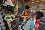 A barber at work in West Fasura, a village on an island in the Brahmaputra River in northern Bangladesh.
