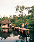 PANAMA, Bocas del Toro, Salt Creek Islands, a Guaymi Indian man and woman stand on a dock in front of their home by the sea , Central America