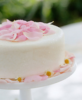 A cake decorated with pink rose petals for a summer afternoon tea