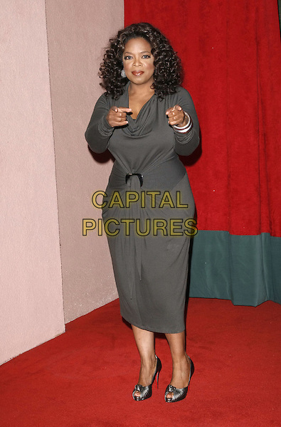 OPRAH WINFREY .at The Hollywood Reporter's Annual Women in Entertainment Breakfast held at The Beverly Hills Hotel in Beverly Hills, California, USA, .December 5th 2008.                                                                     .full length grey gray dress long sleeved Christian Louboutin shoes peep toe shoes fingers pointing .CAP/DVS.©Debbie VanStory/Capital Pictures