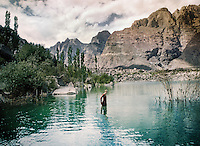 A young woman half way immersed in water at a lake near the Kachura village, in Baltistan province, Karakoram mountains. Pakistan.