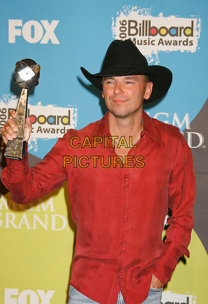KENNY CHESNEY.2006 Billboard Music Awards held at the MGM Grand Hotel and Casino, Las Vegas, Nevada, USA..December 4th, 2006.half length red shirt black hat award trophy.CAP/ADM/RE.©Russ Elliot/AdMedia/Capital Pictures