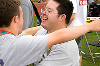 Winning athletes hugging at award ceremony. Special Olympics U of M Bierman Athletic Complex. Minneapolis Minnesota USA