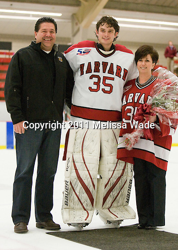 Ryan Carroll (Harvard - 35) poses with his father and mother Maureen Carroll. - The Harvard University Crimson defeated the St. Lawrence University Saints 4-3 on senior night Saturday, February 26, 2011, at Bright Hockey Center in Cambridge, Massachusetts.