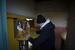 Prescot Cables 2 Brighouse Town 1, 13/02/2016. Hope Street, Northern Premier League. A turnstile operator with a fan entering the ground before Prescot Cables played Brighouse Town in a Northern Premier League division one north fixture at Valerie Park. Founded in 1884, the 'Cables' in their name came from the largest local employer, British Insulated Cables and they have played in their current ground, also known as Hope Street, since 1906. Prescott won the match 2-1 watched by a crowd of 189. Photo by Colin McPherson.