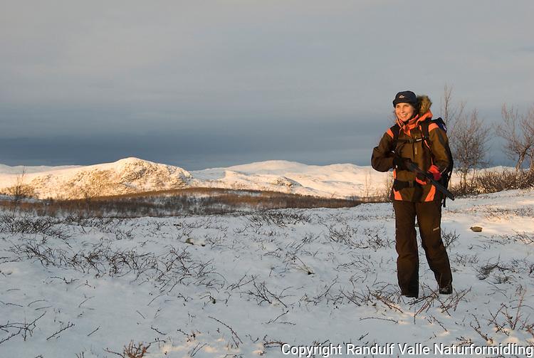 Jente med hagle går på jakt i snø ---- Girl with shotgun hunting in snow covered landscape