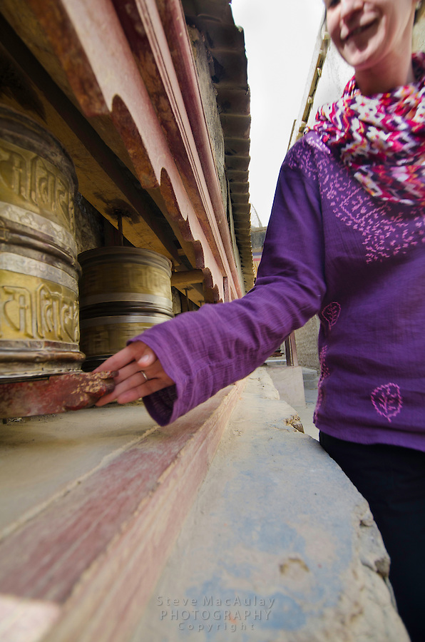 Western traveler spinning prayer wheels, Shey Palace, Naropa Royal Palace, Shey, Ladakh, India.