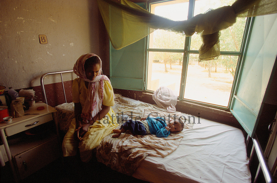 Eritrea - Gash Barka - Mother taking care of her baby at the hospital. As a result of 30 years of war for independence against Ethiopia (from 1961 to 1991) and another 3 years from 1997 to 2000, there are 50,000 Eritreans currently living in internally displaced (IDP) camps throughout the country. These IDPs have fled three times in the last 10 years, each time because of renewed military conflict. They lived in relatives' homes when lucky enough, but mostly, the fled to the mountains, where they attempted to do what Eritreans do best, survive. Currently there is no Ethiopian occupation in Eritrea, but landmines prevent the IDPs from finally going home. .It is estimated that every Eritrean family lost two or three members to the war which makes the reality of the current emergency situation even more painful for Eritreans worldwide. Currently, the male population has been decreased dramatically, affecting the most fundamental socio-economic systems in the country. Among the refugee population, an overwhelming majority of families are female-headed, severely affecting agricultural production. For, IDPs in particular, 80% of households are female-headed..The unresolved border dispute with Ethiopia remains the most important drawback to Eritrea's socio-economic development, as national resources (human and material) continue to be prioritized for national defense. Eritrea is vulnerable to recurrent droughts and variable weather conditions with potentially negative effects on the 80 percent of the population that depend on agriculture and pastoralism as main sources of livelihood. The situation has been exacerbated by the unresolved border dispute, resulting in economic stagnation, lack of food security and increased susceptibility of the population to various ailments including communicable diseases and malnutrition..