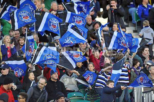 Bath supporters in the crowd wave flags in celebration. LV= Cup match, between Bath Rugby and the Newport Gwent Dragons on November 10, 2012 at the Recreation Ground in Bath, England. Photo by: Patrick Khachfe / Onside Images