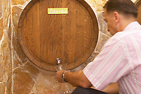 A decorative wine barrel in the winery restaurant and wine bar used to serve white wine Zilavka from tap. A man filling a carafe decanter with wine. Podrum Vinoteka Sivric winery, Citluk, near Mostar. Federation Bosne i Hercegovine. Bosnia Herzegovina, Europe.