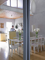 The double-height dining room wall is made of parged concrete, a material normally used on the exterior of buildings, and proved to be a structural and an aesthetic solution