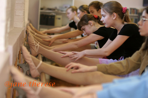 Selene Salem 13 (second from right) and her twin sister Julianne (third from right - both in red hair scrungies), do their barr excersises at the Jane Lopten School of Dance in Landsdale, Pa. on Saturday March 4, 2006. All the Salem children are involved in physical activities of some sort or the other. It improves the childrens bones due to a lack proper nutrition in utero and diet growing up in their orphanage in Russia. Two years ago, the girls could not even do this simple excercise. The Salem children, 3 sets of twins, are from Russia. Sophia and twin Joseph were adopted at 11 months of age by Hythem and his wife Lisa. The other twins, Selene and Julianne 13 along with Sam and Jake, were adopted just 20 months ago. All children are thriving in school, socially and physically. photo by jane therese