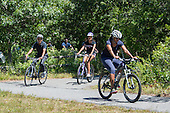United States President Barack Obama, left, daughter Malia Obama, center, and first lady Michelle Obama are followed by security people as they ride their bicycles on the Manuel F. Correllus State Forest bike path outside of West Tisbury, Massachusetts on Friday, August 15,  2014 during their summer vacation.<br /> Credit: Rick Friedman / Pool via CNP