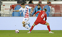 TORONTO, ON - OCTOBER 15: Christian Pulisic #10 of the United States moves past Scott Arfield #8 of Canada during a game between Canada and USMNT at BMO Field on October 15, 2019 in Toronto, Canada.