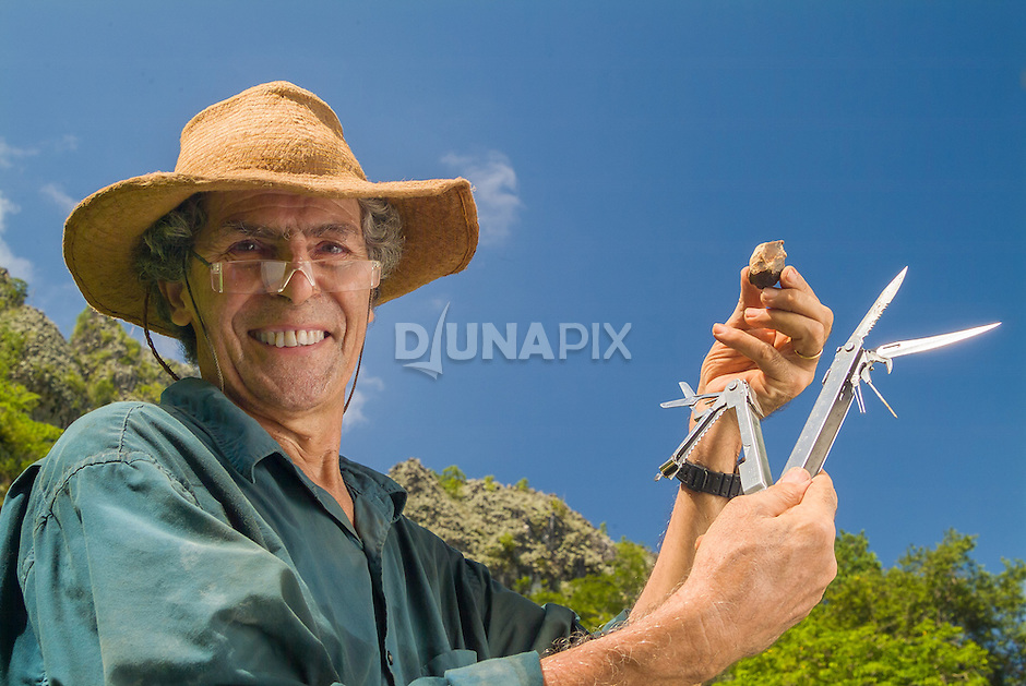 French archaeologist Jean-Michele Chazine playfully compares a modern multipurpose tool with its paleolithic equivalent -- a chert core he found at Kebaboh burial cave in Sangkulirang, East Kalimantan.