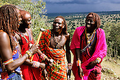 Lolgorian, Kenya. Siria Maasai Manyatta; four moran warriors standing on a hill talking and laughing.