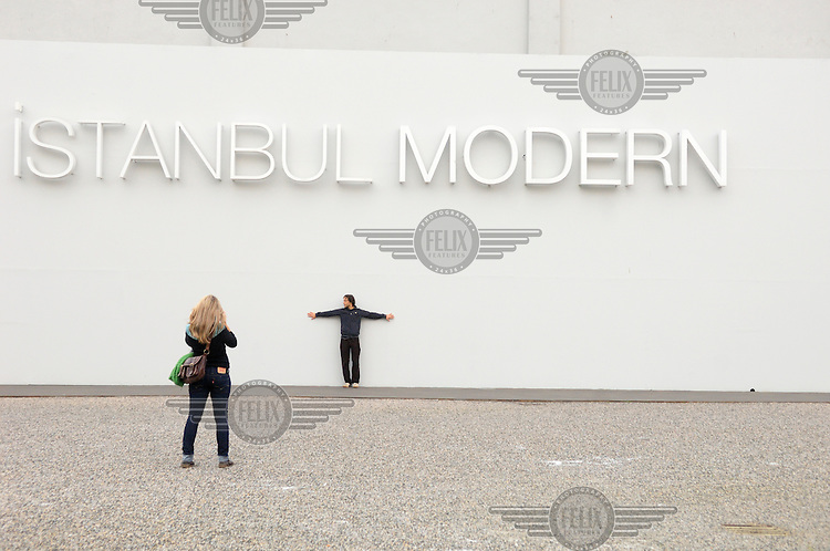 A man posing for a photo under the sign of 'Istanbul Modern', the city's new Twentieth Century art museum housed in a former warehouse by the Bosphorus.