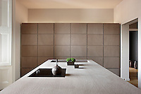 A contemporary, minimalist kitchen with a flush cupboard wall and a central island unit.