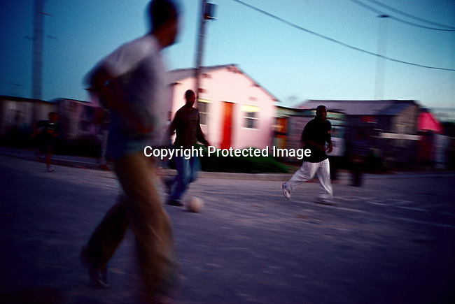 Unidentified men play soccer in the streets on October in Khayelitsha, South Africa, the biggest black township outside Cape Town, South Africa. It's estimated that over one million people live here, most of them under appalling conditions in shacks with no running water or electricity. The township was founded in 1984 and it still attracts people from the rural areas that look for work in Cape Town. Most people don't find work and a lucky few are paid low wages used mostly as maids and day laborers. (Photo by: Per-Anders Pettersson)