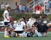 Portland Thorns FC team huddles around injured Portland Thorns FC forward Alex Morgan (13). In a National Women's Soccer League (NWSL) match, Boston Breakers (blue) defeated Portland Thorns FC (white/black), 2-1, at Dilboy Stadium on August 7, 2013.