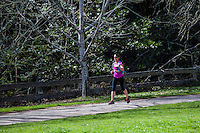 A smiling young woman in running clothes is running along a paved path with trees in the background and green grass in the foreground.
