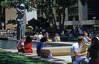 People sitting around a fountain and statue in downtown Honolulu