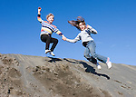 Aurora Alexander 7, and Sophie Marshall 8 jumping off sand dune near Potholes Reservoir in Grant County, WA.