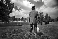 Blues musician Big Ron Hunter stands in a field near his home in Winstom Salem, holding onto his banjo.