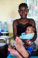 TANZANIA Mara, Tarime, village Masanga, hospital of MARY KNOLL MISSIONARY, young Kuria girl 14 years old with baby after delivery, young girls are often forced to marry elder mans / TANSANIA Mara, Tarime, Dorf Masanga, Krankenhaus der MARY KNOLL MISSIONARE, junges Kuria Maedchen(14 Jahre alt) mit Baby nach Entbindung, junge Maedchen werden oft an aeltere Maenner zwangsverheiratet