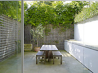 The limestone kitchen work top and cupboards extend out seamlessly into the courtyard garden
