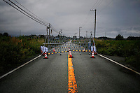 A road block prevents people from entering highly contaminated zone in the evacuated town of Namie in Fukushima prefecture September 13, 2013. Namie's more than 20,000 residents can visit their homes once a month with special permissions but are not allowed to stay overnight inside the exclusion zone. A total of 160,000 people had been forced to leave their homes around Daiichi plant after the government ordered the evacuation following the nuclear disaster in March 2011.  REUTERS/Damir Sagolj (JAPAN)