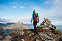 Female hiker walks near summit cairn on Reinebringen, Lofoten Islands, Norway