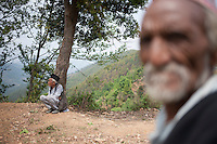 A survivor of Nepal earthquake sits under a tree near at Jalkeli village, outskirts of Kathmandu, Nepal. May 1, 2015