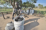 Faustino Duku is the United Methodist pastor in the Southern Sudan village of Ligitolo, but he earns his living producing and selling charcoal, which he bags up here to prepare for transport to the market in the nearby town of Yei. Families here are rebuilding their lives after returning from refuge in Uganda in 2006 following the 2005 Comprehensive Peace Agreement between the north and south. NOTE: In July 2011, Southern Sudan became the independent country of South Sudan