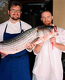 USA, California, Los Angeles, portrait of Chef Michael Cimarusti and sous chef holding a fish at his restaurant Providence.
