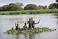 Children floating on a bundle of water-hyacinths on the Sobat river.