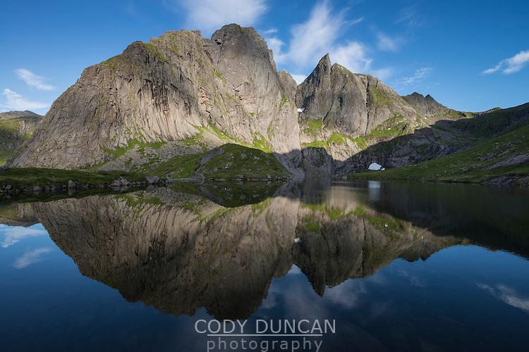 Multiple summits of Munken mountain peak reflect in lake, Moskenesøy, Lofoten Islands, Norway