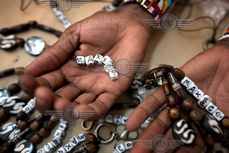 """Maasai women make key rings for the Italian fashion brand MAX & Co. at the Marula Studios in Nairobi. The Maasai tribe are renowned for their expert bead work and as such have been hired to help create part of MAX & Co.'s """"ethical fashion"""" range. The limited edition collection consists of a range of handmade accessories such as shoulder bags, bracelets, key-rings, belts and scarfs."""