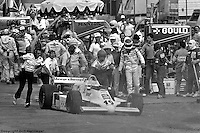 Bobby Rahal watches as his car is pushed from the pit lane after a fire started following a pit stop in the 1982 IndyCar race at Phoenix International Raceway near Phoenix, Arizona.