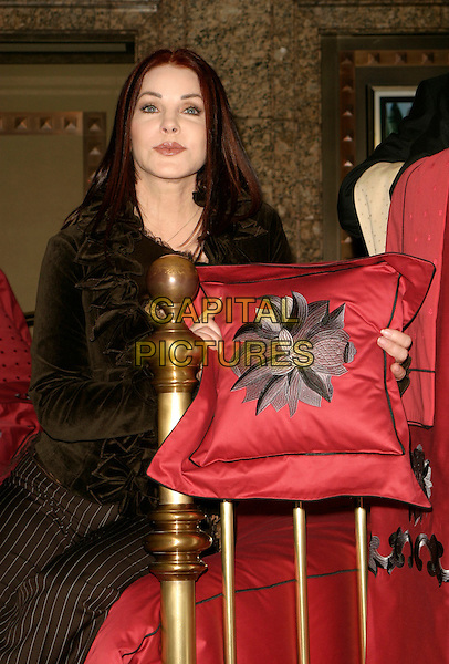 PRISCILLA PRESLEY.Press launch & photocall, Bed Linen department (2nd floor), Harrods, London, UK..April 5th, 2006.Ref: AH.half length red burgundy pillow.www.capitalpictures.com.sales@capitalpictures.com.© Capital Pictures.
