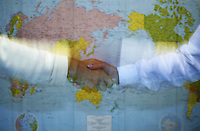 Shaking hands against a world map