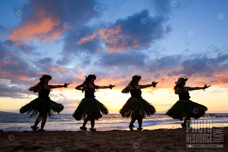 Silhouette of hula dancers at suset at Palauea Beach, Maui, Hawaii.