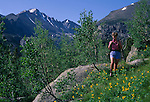 Woman hiking along trail with Longs Peak in background, Rocky Mtn Nat'l Park ,CO