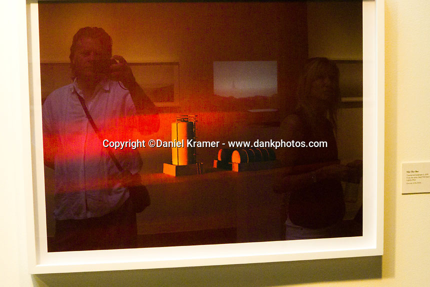Self portrait reflected in a photo at FotoFest in Houston, Texas while leading my Rice University Continuing Education photography class on a field trip in 2013.