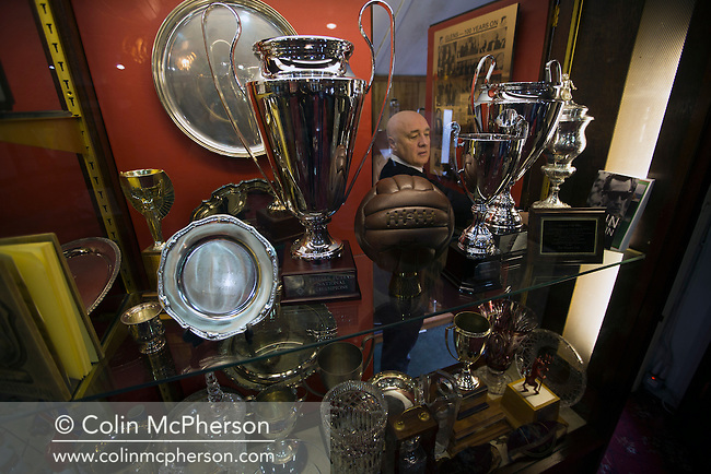 Club secretary Ricky Rea adjusts the trophy cabinet display in the boardroom at The Oval, Belfast, pictured before Glentoran hosted city-rivals Cliftonville in an NIFL Premiership match. Glentoran, formed in 1892, have been based at The Oval since their formation and are historically one of Northern Ireland's 'big two' football clubs. They had an unprecendentally bad start to the 2016-17 league campaign, but came from behind to win this fixture 2-1, watched by a crowd of 1872.